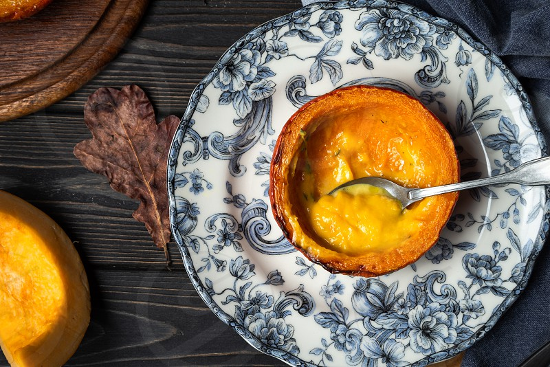Baked creamy pumpkin soup served in a halved small pumpkin on a vintage plate on rustic wooden background top view horizontal orientation photo