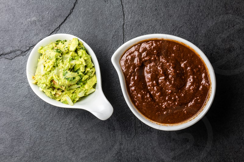 Traditional famous mexican sauces chocolate chili mole poblano and avocado guacamole on slate gray background. photo