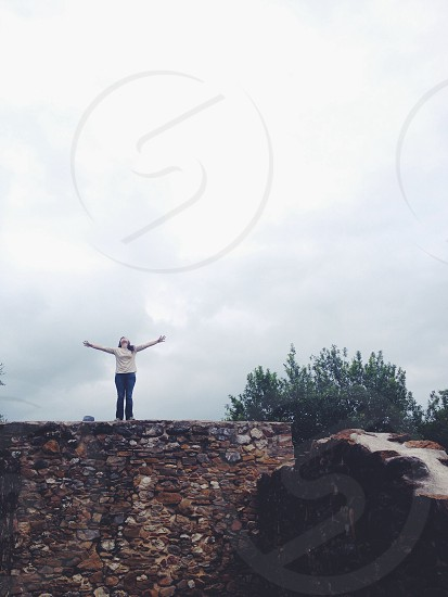 woman standing on stone wall with arms stretched out under gray sky photo