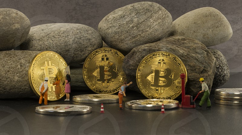 little figures putting the bitcoins in a saf solid as a rock photo