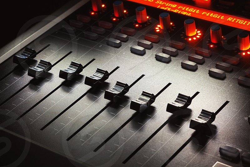 Faders of a modern mixing console music studio equipment details.  photo