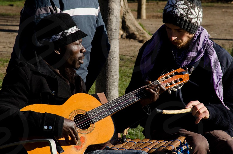 two men in hats outside with man in fedora playing tan acoustic guitar photo