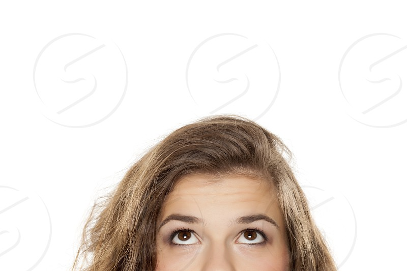 half portrait of a young girl looking up on white background photo