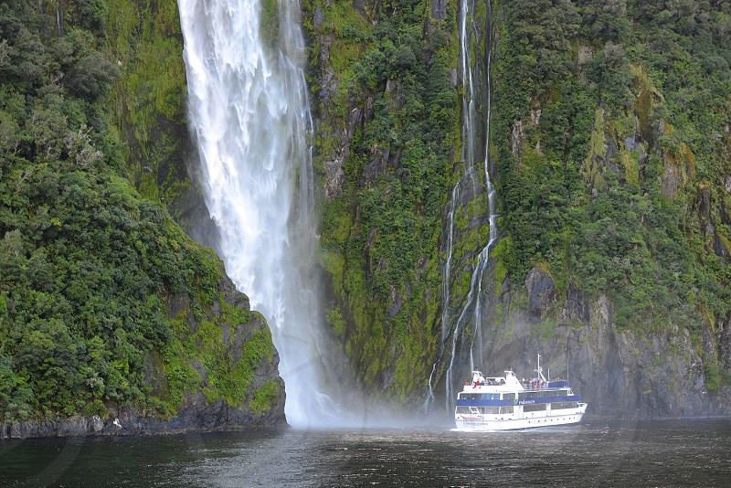 Boating boat cruise waterfalls landscape scenic nature nature lovers New Zealand Milford sound water sea Tasman sea fjordlands nautical boats sail away sailor places transportation tourists photo