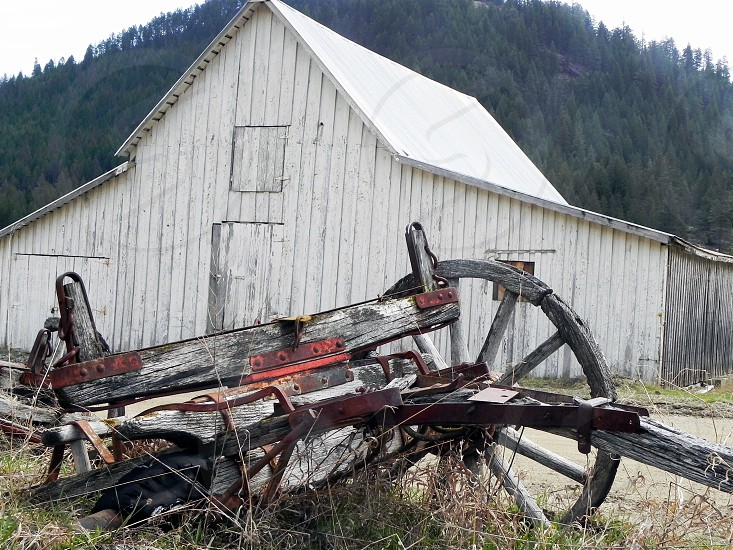 Antique farm equipment in front of an old white barn. photo