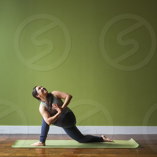 A young woman smiling while in a yoga pose against a green backdrop during the day. photo