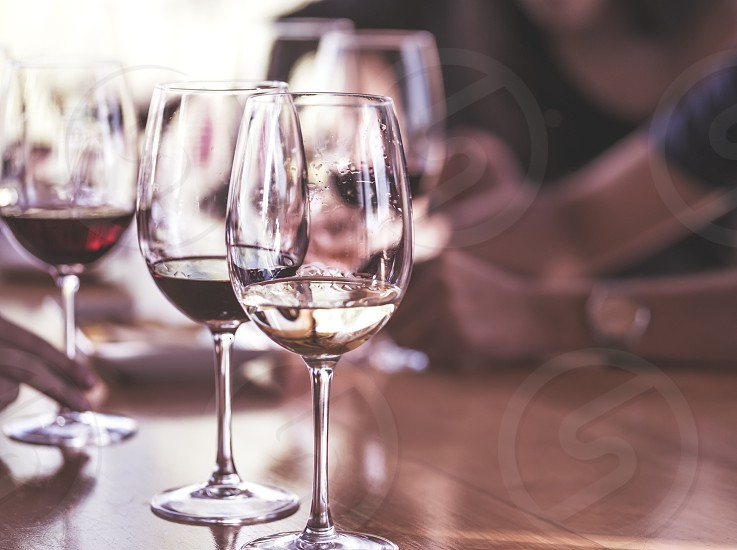 Wineglasses with white and red wine on wooden table on bright background photo