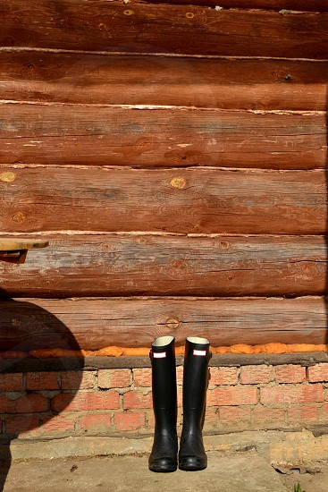 A pair of black rubber boots standing by a wall of a brightly lit log house on a sunny day photo