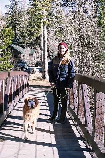man wearing blue jacket holding short-coated brown dog standing on brown bridge photo