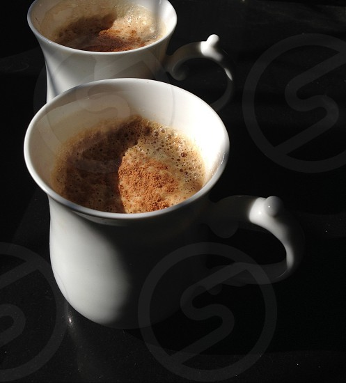 Hot coffee for two with a dash of cinnamon clicked in natural light  photo