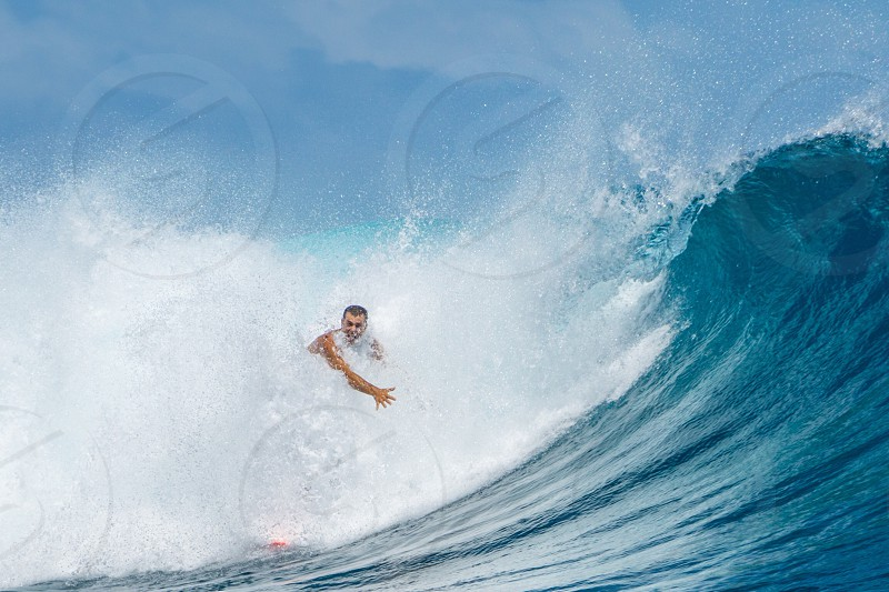 man surfing against ocean wave getting hit by splashes during day time photo