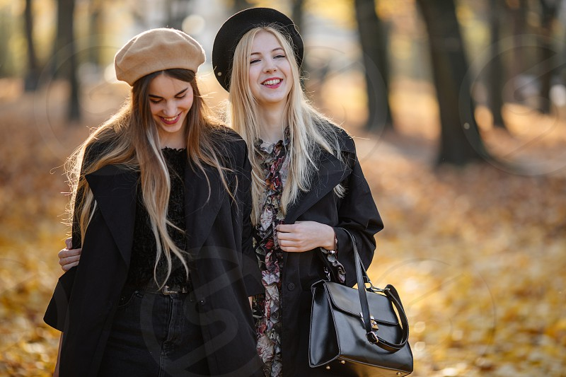 Two pretty girls walk on the city street talk and smile to each other photo