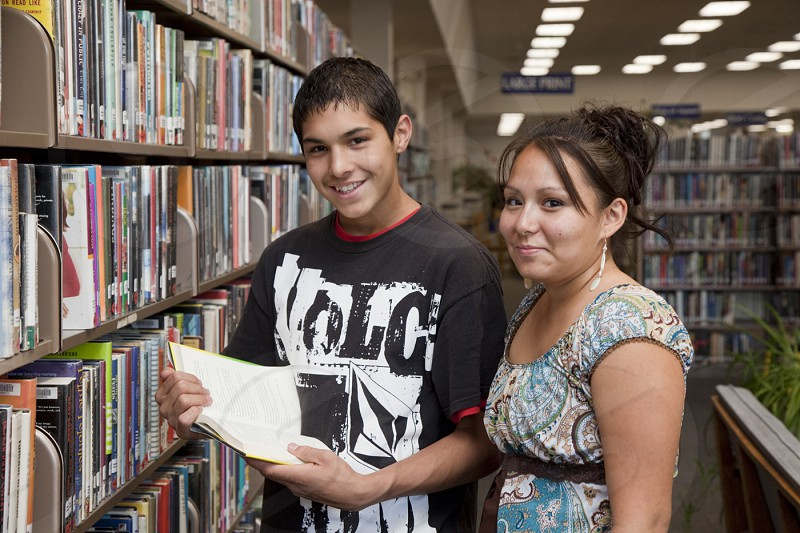Two Native American teenagers share a book next to a book shelf while visiting a library. photo