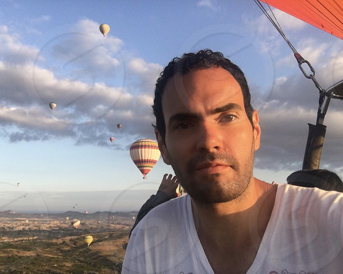 Cappadocia Turkey hot air balloon portrait man young adult caucasian man looking at the camera incidental people one man only clouds sky inside flying adventure serenity calm peaceful  photo