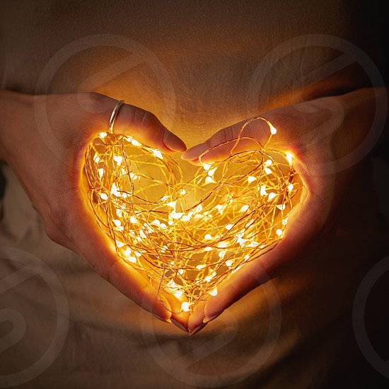 Close-up of lights in the shape of a heart a woman holding in hands in the dark. The concept of a Valentine's Day photo
