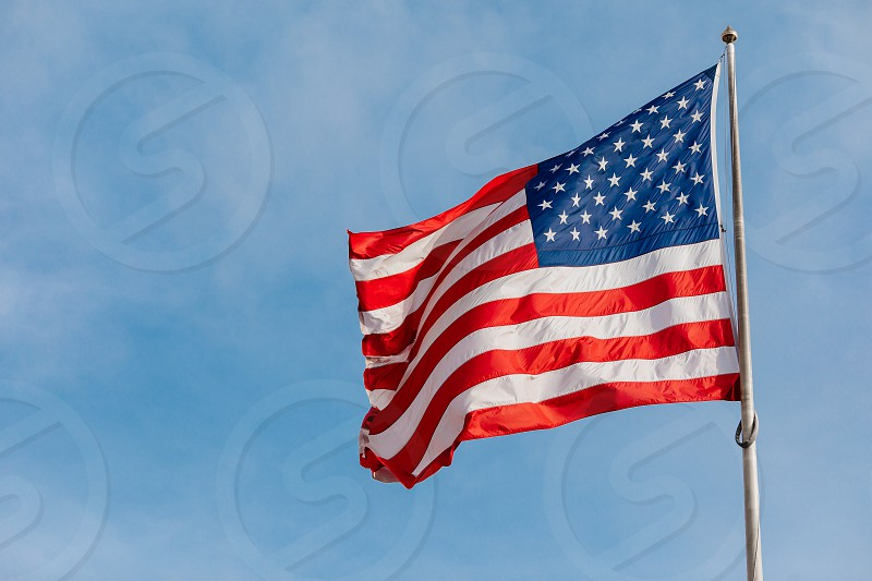 American flag on the blue sky with clouds photo