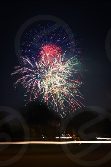 fireworks display under green trees beside street with cars lights in long exposure photography during night time photo