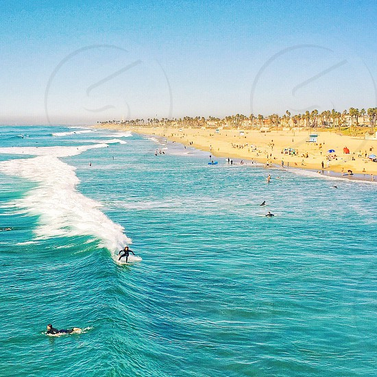 person surfing on blue white water wave under white cloudy blue sky during daytime photo