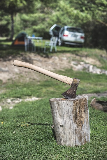 Ax stuck on a stump in the forest. Tent and car on background photo