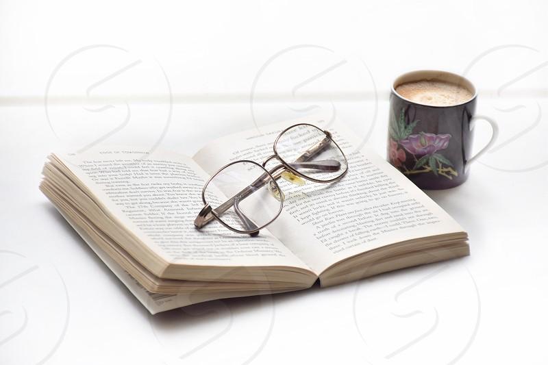black frame eyeglasses on open book photo