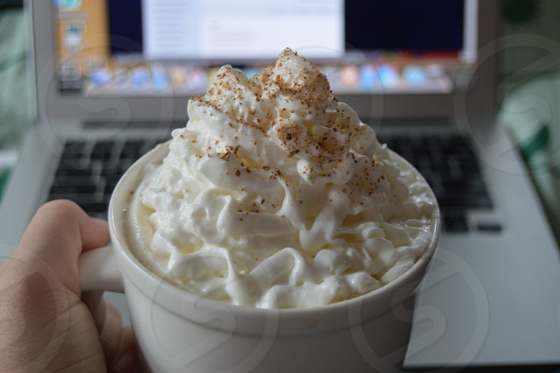 white icing on top of white ceramic cup in front of apple macbook pro photo