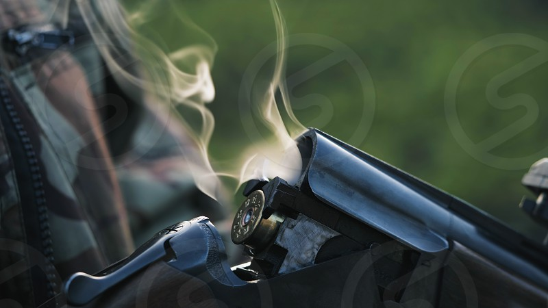 Smoke from the trunks of smooth-bore hunting rifle after firing. Hunter in camouflage takes out cartridges from a gun photo