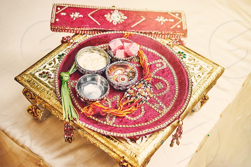 The red velvet on gold decoration table of prayer items for thread ceremony (puja pooja) of Indian wedding photo