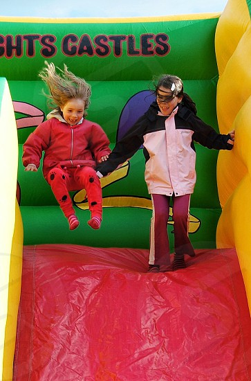 two children sliding down inflatable slide photo