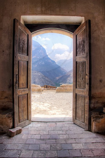 The large wooden doors of an ex-convent located in the hills of Queretaro in Mexico looking out on to a canyon in front. photo