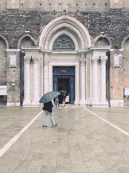 Church umbrella rain outside pedestrian Venice Italy architecture wet rainy photo