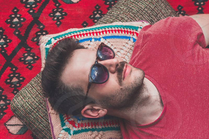 Handsome hipster lying on rug outside in the garden photo