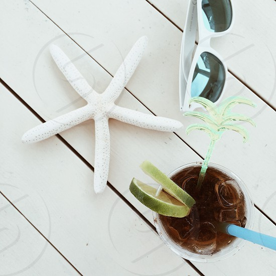 dried white starfish between white framed wayfarer sunglasses and glass of iced tea with lime and blue straw on white wooden platform photo