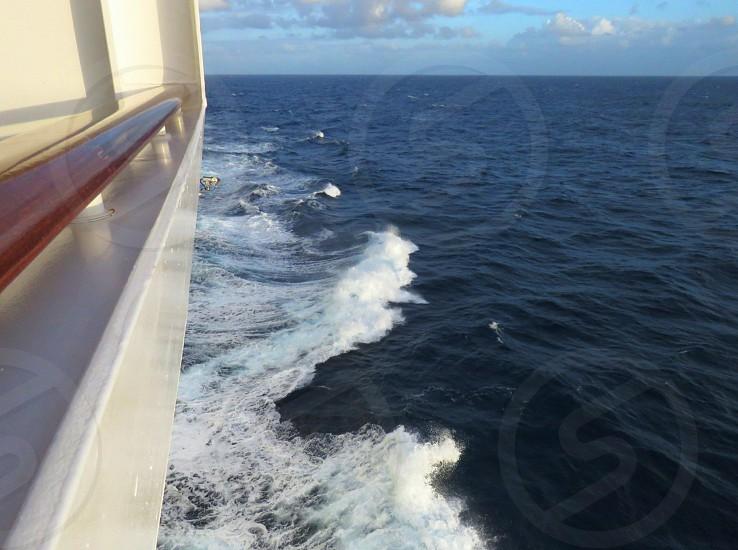 Sailing Caribbean water  ocean adventure high seas white boat wooden rail wake landscape clouds photo