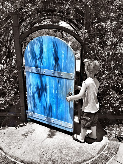 boy standing near blue and gray gate photo