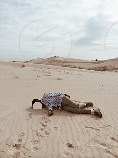 person in white and black button down long sleeved shirt and brown pants lying on white sand photo