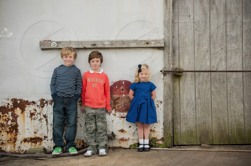 two boys and a girl leaning against a wall photo