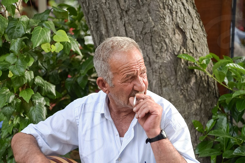 man in white button down shirt smoking cigarette photo