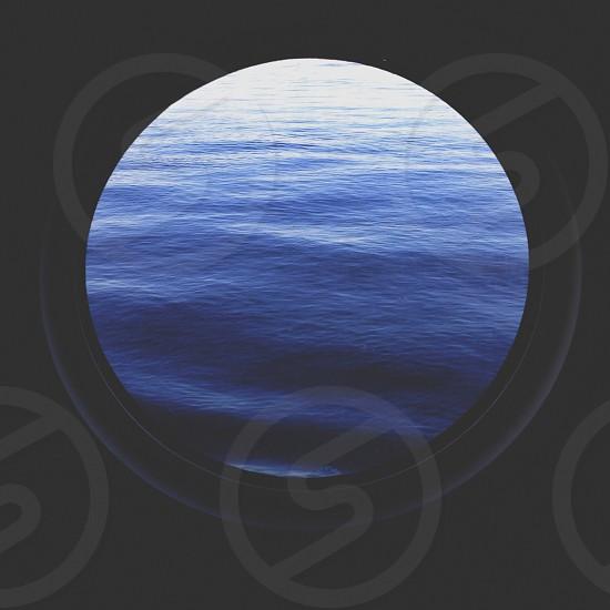 porthole window facing blue waves photo