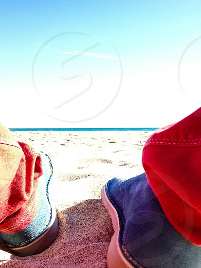 Sitting on a beach in blue suade shoes photo