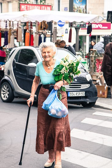 One of my favorite memories in Paris. A beautiful and classy French woman crossing the street as my husband and I were heading to the metro station. Her gracious smile French outfit the flowers in her hands couldn't get more Parisian! Couldn't help but smile back at her! photo