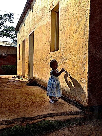 The child watch house wall shadow cute child girl africa photo