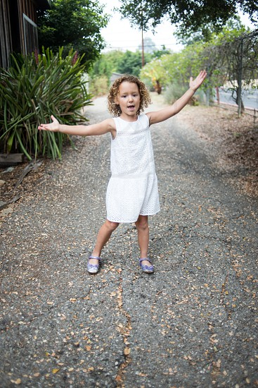 little curly-haired girl singing and dancing to Frozen songs photo