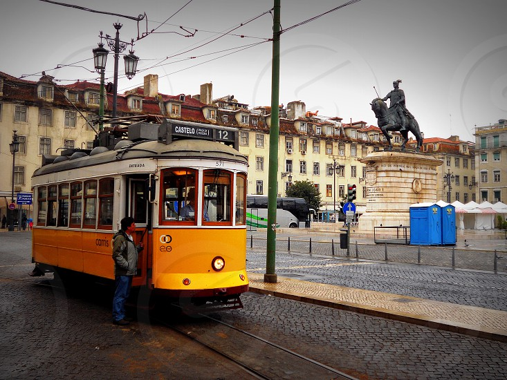 trolley car near european buildings and statue photo