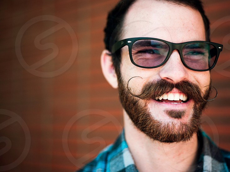 A young man with glasses and a large twirled mustache bears a large grin in from of a brick wall. photo