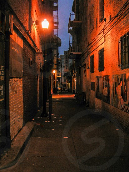 night photography of narrow road between brown buildings with sconce photo