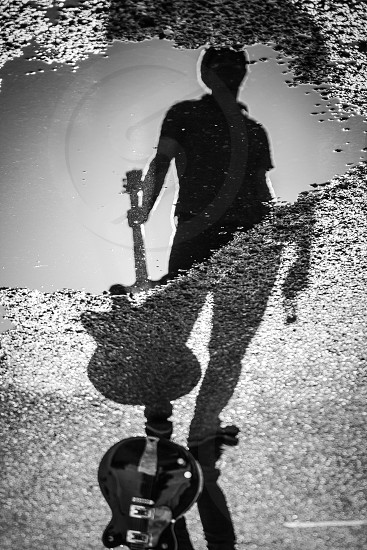 Musicians point of view guitar shadow person standing with guitar puddle photo