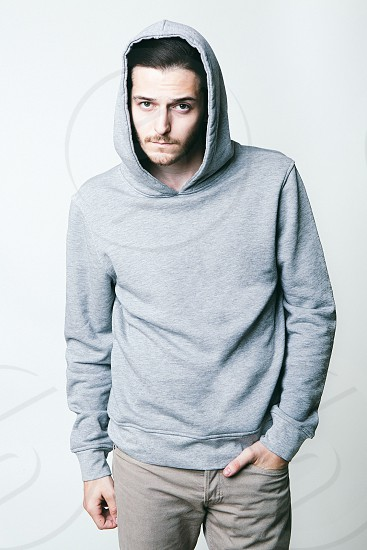 man wearing a grey hoodie hand in his pocket photo