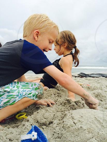 boy playing sand on beach photo