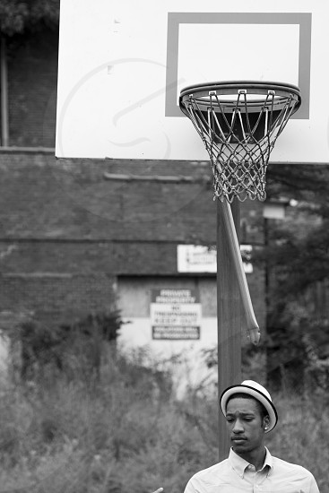 man in white fedora hat in front of basketball hoops photo