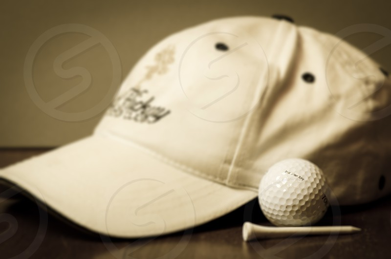 golf hat cap ball tee pin pin blurred wooden table sport photo